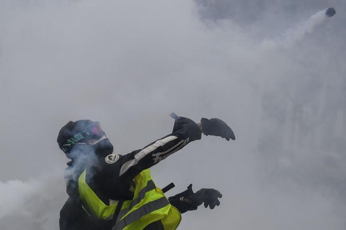 Un manifestant relance une grenade lacrymogène de base vers les forces de l'ordre, le 12 janvier à Paris.