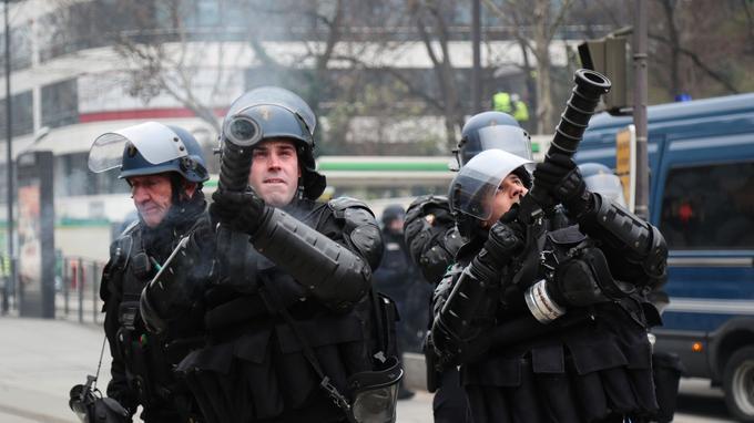 Des gendarmes mobiles lancent des grenades à l'aide d'un lanceur, à Paris, le 29 décembre.