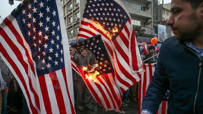 Des Iraniens brûlent des drapeaux américains en marge des cérémonies du 40e anniversaire de la Révolution de 1979, lundi, à Téhéran.