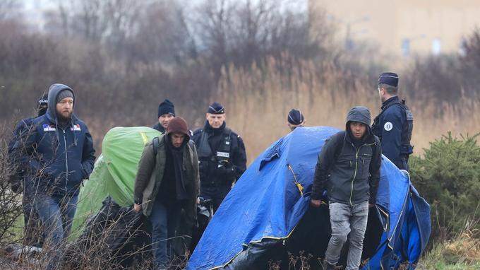 Deux migrants sont encadrés par les forces de l'ordre après le démantèlement d'un camp près de Calais, le 25janvier.