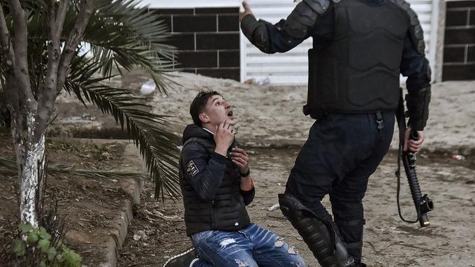 Un jeune Algérien est assis à genoux sur le sol devant un membre des forces de sécurité algériennes.