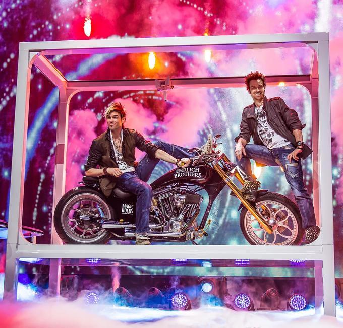 Les deux frères font jaillir une moto d'un iPad géant.