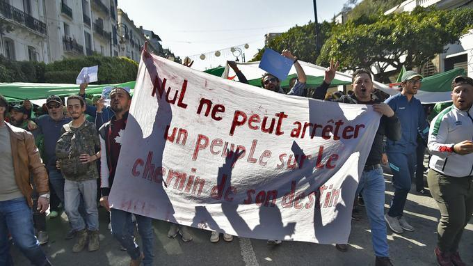 Des Algériens marchent avec une banderole de protestation: «nul ne peut arrêter un peuple sur le chemin de son destin».
