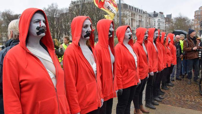 Des manifestantes portant une cocarde tricolore (invisible sur la photo) sur leur capuchon, emblème de la Révolution française, se tiennent debout la bouche bandée.