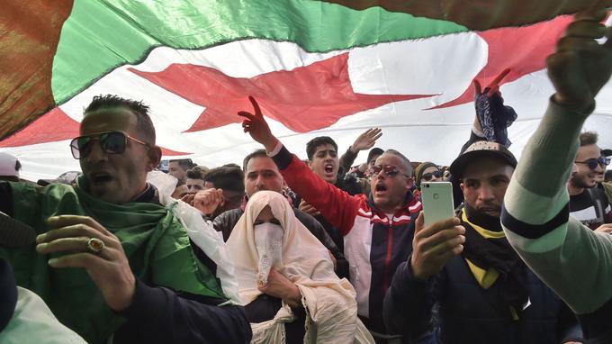 Des Algériens chantent des slogans sous un drapeau national.