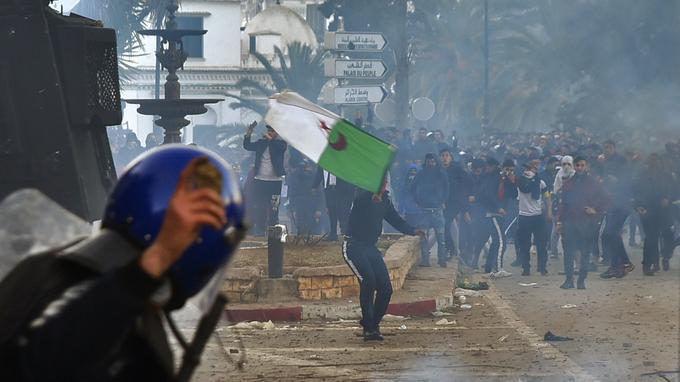 Un membre des forces de sécurité algériennes tient une pierre dans sa main alors que les forces antiémeutes se rassemblent dans la capitale.