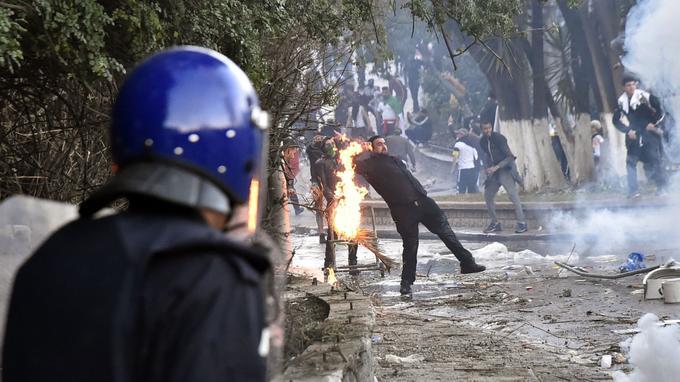 Des flammes éclatent près d'un homme alors que des membres des forces de sécurité algériennes répondent aux protestations.