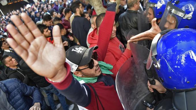 Un manifestant algérien se tient les mains en l'air devant les membres des forces de sécurité.
