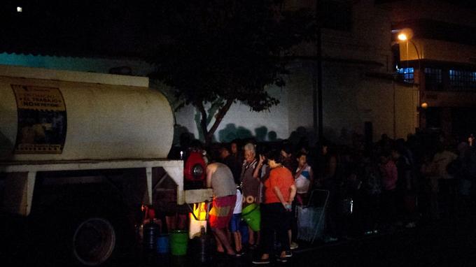 Distribution d'eau, dans le noir, à Caracas.