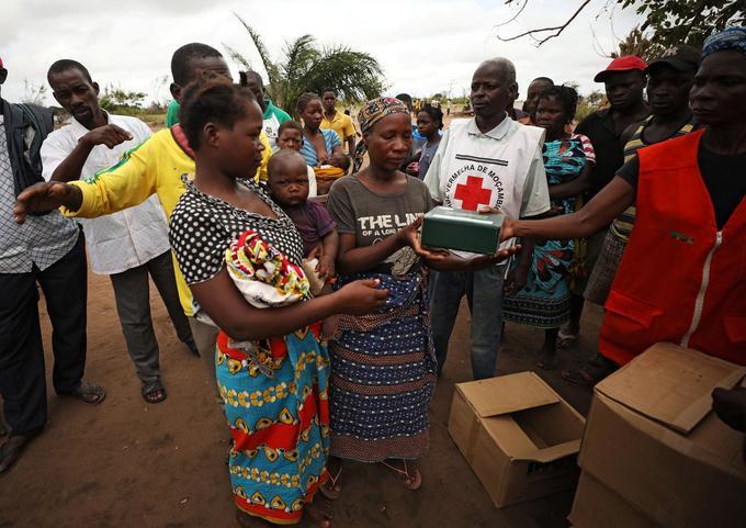Une femme attend avec son enfant pendant que l'aide est distribuée dans un camp.