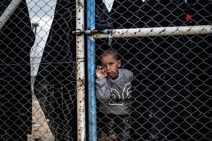 Un enfant attend derrière une porte grillagée.