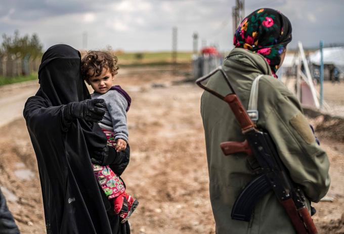 Une femme avec un enfant, pointe du doigt une combattante des Forces démocratiques syriennes.