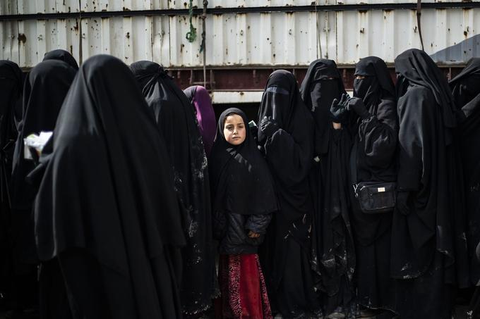 Des réfugiées irakiennes et des femmes syriennes déplacées font la queue pour recevoir des marchandises.
