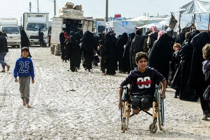 Des femmes voilées font la queue pour recevoir des marchandises dans le camp.
