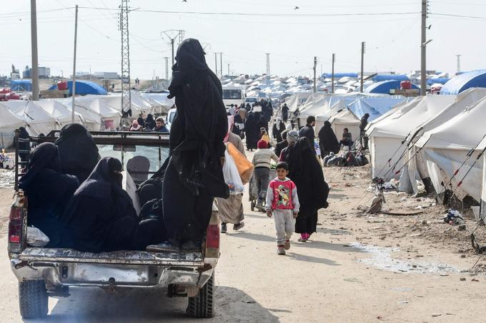 Des femmes voilées montent dans une camionnette dans le camp.