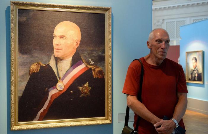 Un visiteur de l'exposition de Fabrizio Birimbelli à Saint-Pétersbourg pose à côté du portrait de Zinédine Zidane.
