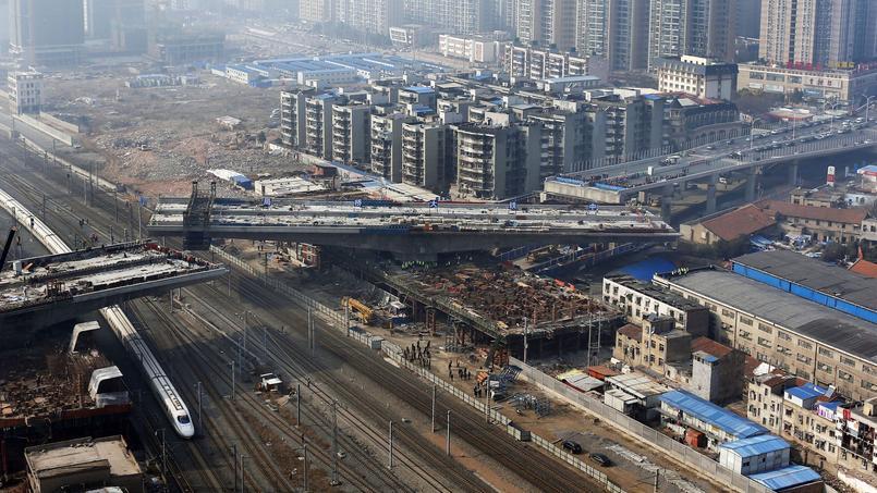 Un train passe sous une passerelle en construction à Wuhan (province de Hubei), le 14 janvier 2014.