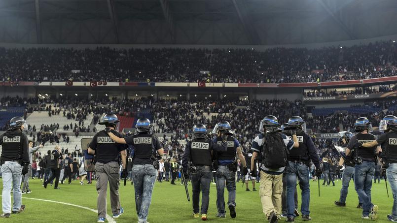 Les forces de police repoussent les spectateurs qui ont envahi le terrain avant le match.