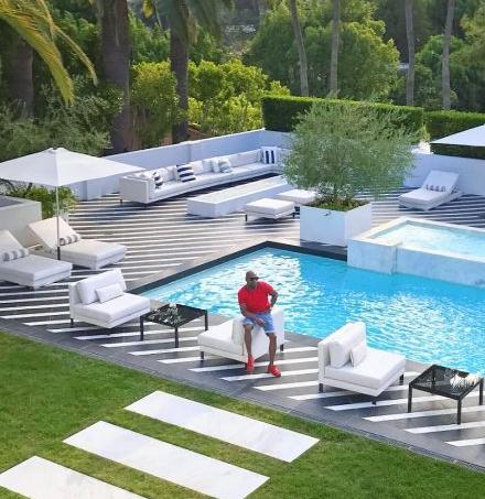 Le champion invaincu pose devant la piscine de sa mirifique villa.