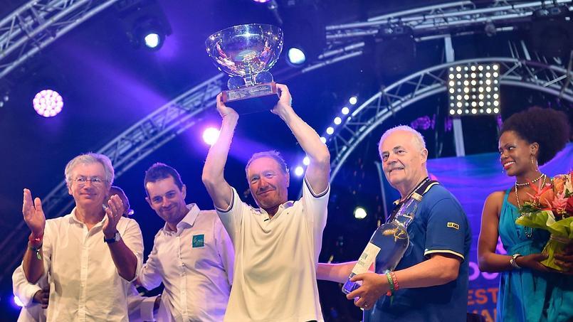 Francis Joyon soulevant le Trophée de la Route du rhum à l'arrivée à Pointe-à-Pitre.