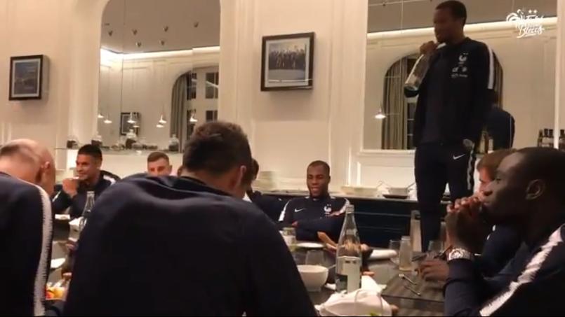 Alassane Pléa chantant devant ses nouveaux coéquipiers de l'équipe de France ainsi que le staff de Didier Deschamps.
