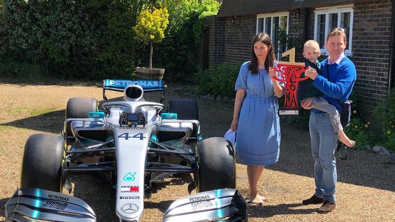 Le jeune Harry Shaw, qui a ému Lewis Hamilton, et ses parents posent à côté d'une monoplace du Britannique