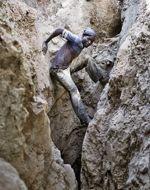 À la force des bras, ce mineur se prépare à descendre au fond du puits.