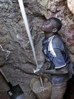 À plus de 10 m de profondeur, le mineur monte un à un les seaux de terre.