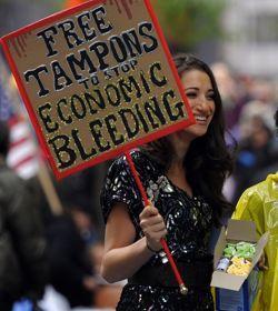 Une manifestante du mouvement Occupy Wall Street à New York brandit une pancarte réclamant la gratuité des tampons, en 2011.