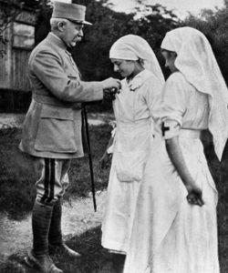 Le General Pétain décore de la Croix de guerre une dame de la Croix Rouge blessée dans les bombardements.