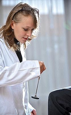 Jeune médecin généraliste testant les reflexes d'un patient. (Illustration)
