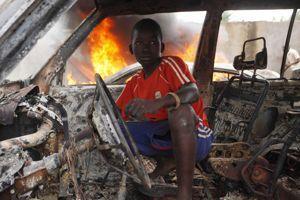 Un jeune Centrafricain dans la carcasse d'un véhicule, à Bangui.