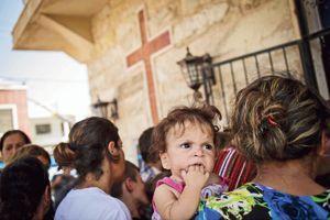 Les familles chrétiennes ayant trouvé refuge dans l'église de Mar Elias, dans le quartier d'Ankawa à Erbil, font la queue dans l'attente d'une aide humanitaire.