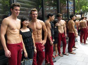 Des vendeurs, torse nus comme le veut la règle des boutiques Abercrombie & Fitch, posent avec des clients à Singapour en 2011.