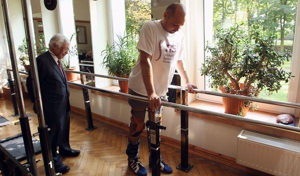 Opéré il y a deux ans, ce n'est que 6 mois après l'opération et de nombreux efforts que le patient a été capable de marcher avec l'aide de barres parallèles et d'attelles.