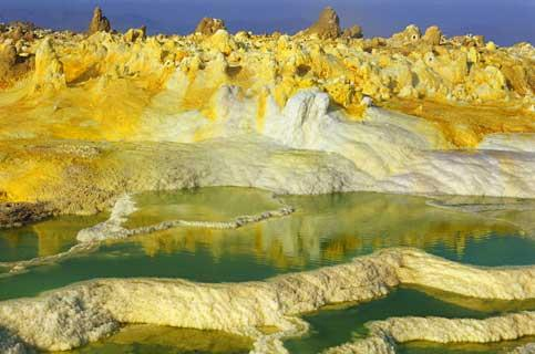 Au coeur du Dallol, une région de l'Afar, dans le nord de l'Ethiopie, est né un cratère volcanique unique au monde. Résultat de l'explosion d'une immense chambre magmatique de la vallée du Grand Rift, il se trouve audessous du niveau de la mer, dans la dépression de Danakil. Dans cette vaste zone saline, ses abords sont hérissés de centaines de cheminées de fées et festonnés d'innombrables sources chaudes, de geysers, de fumerolles, de dépôts de sel et de soufre, de terrasses et de coulées. La chaleur peut y atteindre 60 °C. Lentement, le sel se mélange aux minéraux volcaniques et crée de fragiles concrétions aux formes baroques, hérissées comme un défi aux lois de la géologie.( PHOTO : STEPHAN GLADIEU)