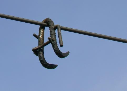 Un fer à béton ouvragé en forme de crochet est arrimé au câble de la caténaire, situé à sept mètres de hauteur le long de la voie. Un système de verrouillage bloque le fer et l'empêche de tomber au premier choc.