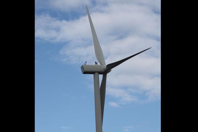 Perchées au sommet de la nacelle à 90 m de hauteur, les deux silhouettes humaines donnent une idée de l'échelle d'une grande éolienne terrestre, ici un modèle Vestas d'une puissance nominale de 2 mégawatts (MW) à Patay (Loiret) près d'Orléans, exploitée par le groupe portugais EDP Renewables.