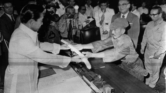 1974. Hiroo Onoda remet son sabre au président Marcos. S'il aurait tué une trentaine de Philippins, le président lui pardonne.
