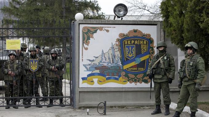 Des hommes en armes, vraisemblablement des soldats russes, encerclent la base ukrainienne.