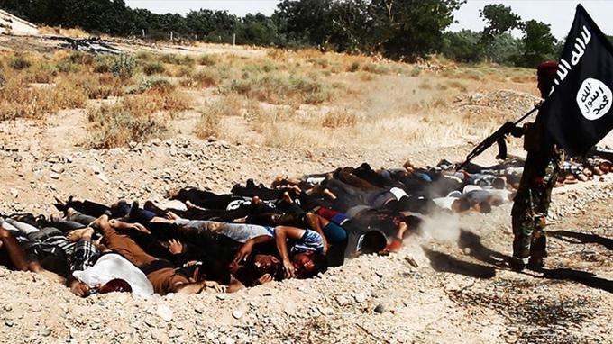 Un insurgé de l'EIIL semble exécuter des hommes en civil alignés dans une fosse, et présentés comme des déserteurs de l'armée irakienne, dans un endroit inconnu de la province de Salah ad-Dine.