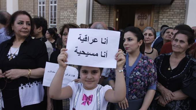 La jeune fille tient une pancarte sur laquelle on peut lire: «Je suis une Irakienne, je suis une chrétienne», le 20 juillet devant l'église de Mar Girgis à Bagdad. Les chrétiens de Mossoul ont reçu le soutien d'autres communautés à travers le pays.
