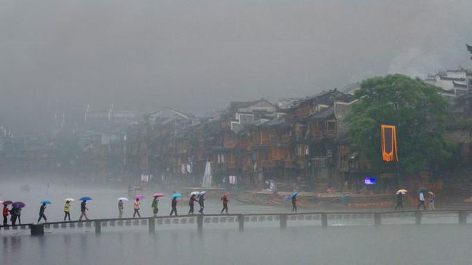 La magie opère sur la vielle ville de Fenghuang quand tombent les pluies torrentielles du printemps. Les maison sur pilotis se dressent en rangs serrés face aux caprices de la rivière Tuo Jiang.