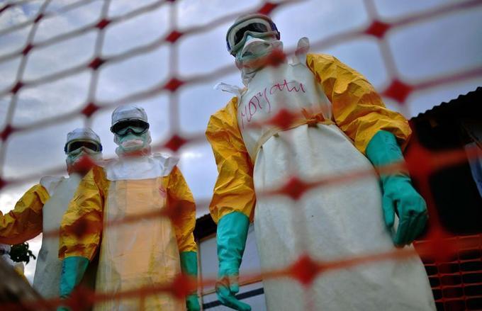 Des membres du personnel médical de Médecins Sans Frontières (MSF) dans leurs tenues de protection traitent le corps d'une victime d'Ebola à Kailahun, en Sierra Leone, une ville située à l'épicentre de l'épidémie.