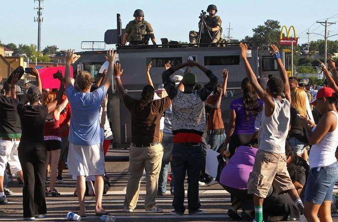 Face à la police lourdement armée, les manifestants lèvent symboliquement les mains en référence à Michael Brown, qui aurait été tué par l'agent de police Daren Wilson tandis qu'il avait les mains levées en signe de reddition.