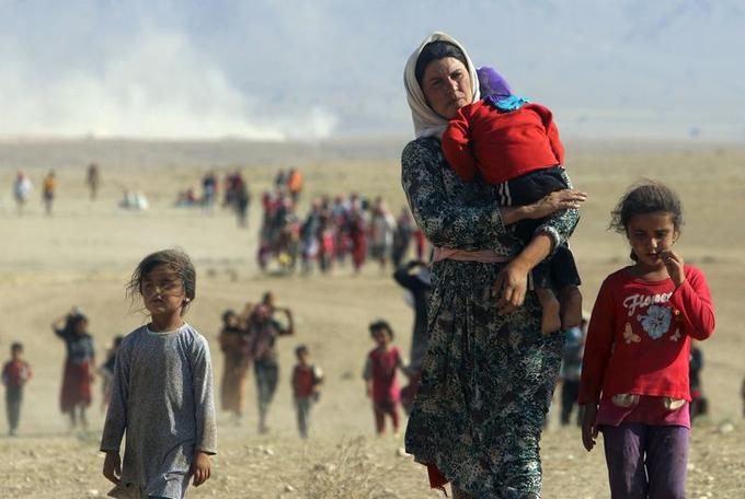 Pour fuir les persécutions des djihadistes de l'État Islamique, des membres de la minorité chrétienne des Yazidis de Sinjar marchent en direction de la frontière syrienne, le 11 août 2014.
