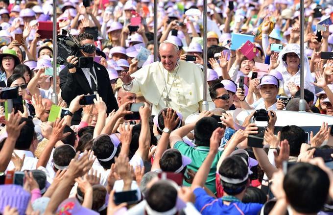 Des fidèles catholiques accueillent le pape François à son arrivée sur la place Gwanghwamun dans le centre de Séoul, le 16 août 2014.