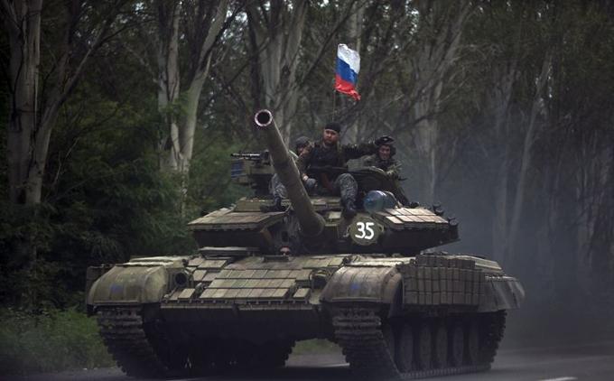 Des rebelles prorusses conduisent un tank sur une route à l'est de Donetsk, lundi 21 juillet 2014.