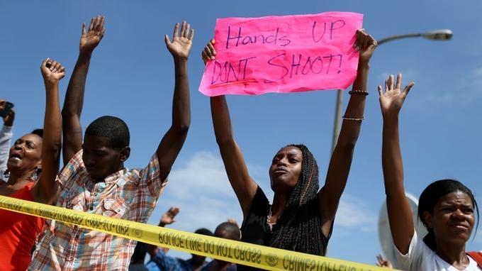 Des manifestants lèvent leurs mains en scandant «Hands up, Don't shoot» («Mains en l'air, ne tirez pas»). Ils adressent leur soutien aux proches de Michael Brown, jeune noir-Américain atteint de six balles tirées par la police, et dénoncent les violences policières.