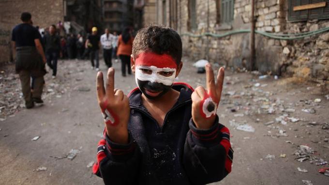 Un jeune garçon arbore les couleurs égyptiennes sur son visage et ses mains faisant le signe «V» de la victoire, en novembre 2011.